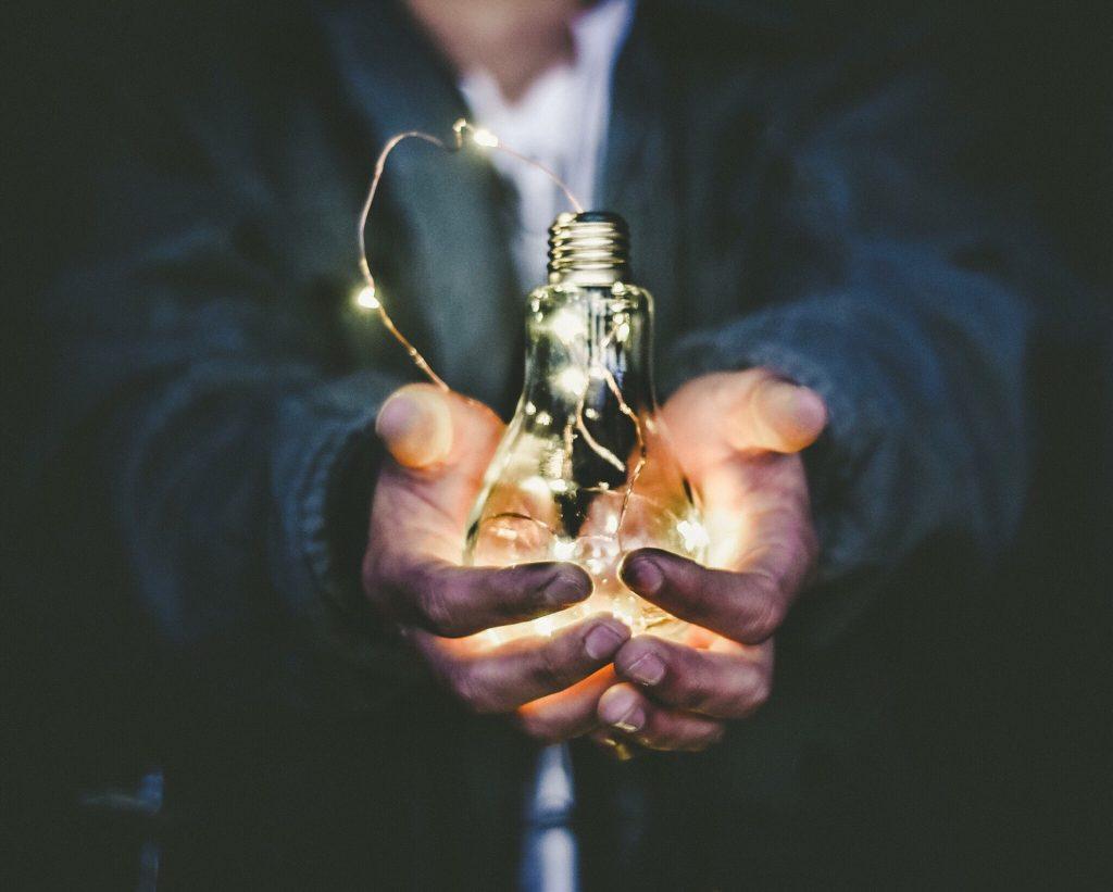 Man holding a lightbulb to represent having an idea